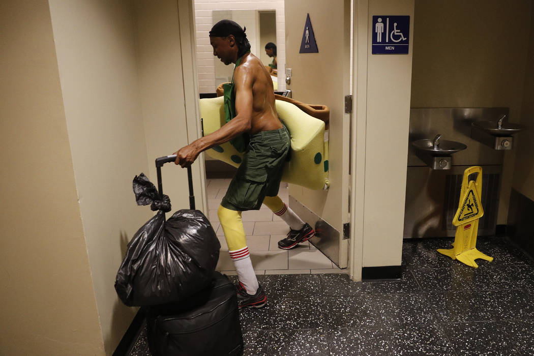Covered in sweat, impersonator Belnarr Golden enters a public restroom with his SpongeBob SquarePants costume folded in half after working on Hollywood Boulevard in Los Angeles on Monday, April 17 ...