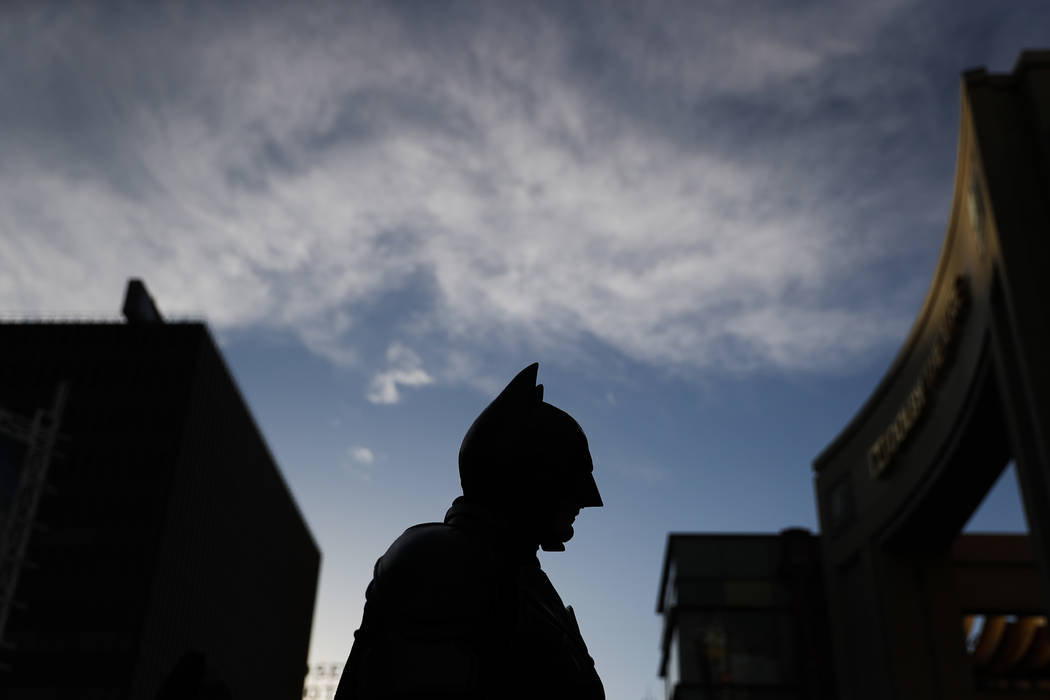 Batman impersonator Matthias Balke is silhouetted while standing on Hollywood Boulevard near the Dolby Theatre in Los Angeles on Thursday, March 2, 2017. Wearing his $3,000 Batman costume, Balke s ...