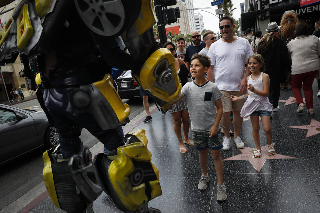 Ramiro Rodriguez in a Bumblebee costume, a character from the Transformers movie series, shakes hands with young tourists on Hollywood Boulevard, in Los Angeles on Friday, May 26, 2017. The 39-yea ...