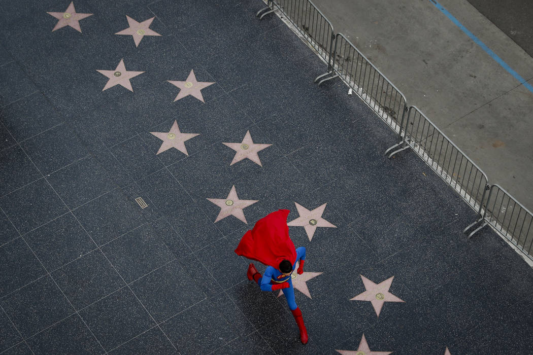 Wearing a Superman costume, Toly Shtapenko, of Ukraine, takes a long stride along the Hollywood Walk of Fame to impress tourists, in the Hollywood section of Los Angeles on Thursday, March 2, 2017 ...