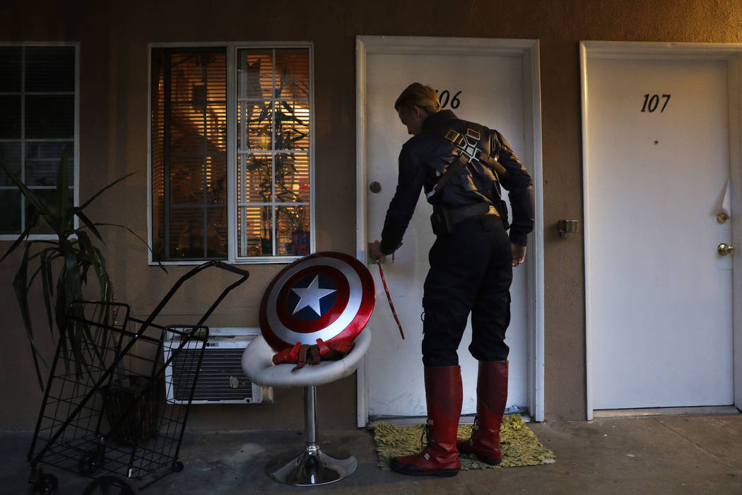 Captain America impersonator Henry Hodge, a cinematographer from England who lives a stone's throw away from Hollywood's Dolby Theatre, opens his apartment door in Los Angeles on Monday, May 8, 20 ...