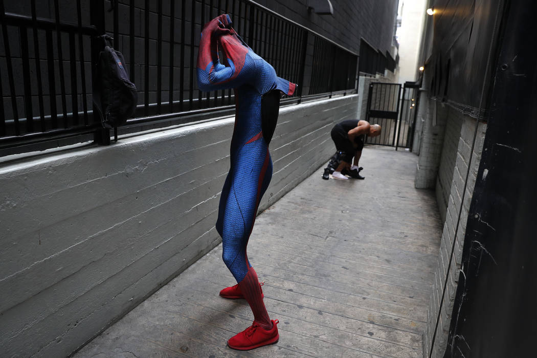 Two Spider-Man impersonators, Rashad Rouse, front, and Juan Carlos Banegas, an immigrant from Honduras, change in the alley next to the TCL Chinese Theatre after working on Hollywood Boulevard in  ...