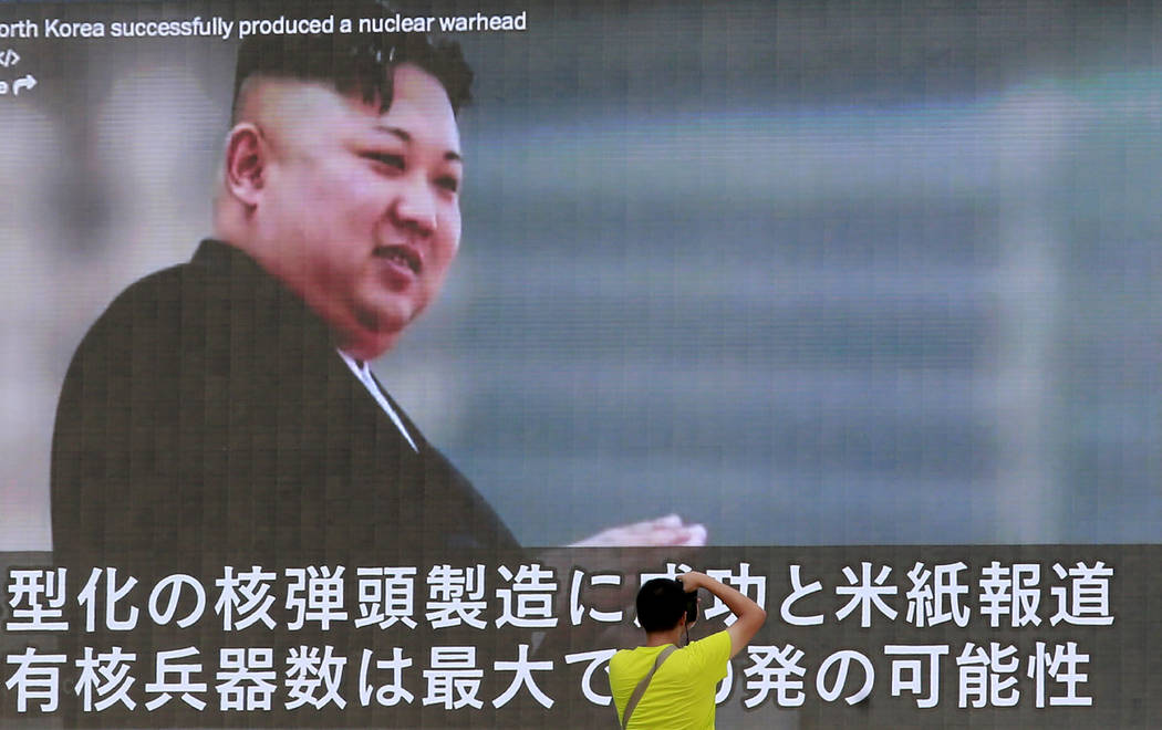 A man takes a photo of a TV news program showing an image of North Korean leader Kim Jong Un while reporting North Korea's rocket launch in Tokyo, Wednesday, Aug. 9, 2017. In an exchange of threat ...