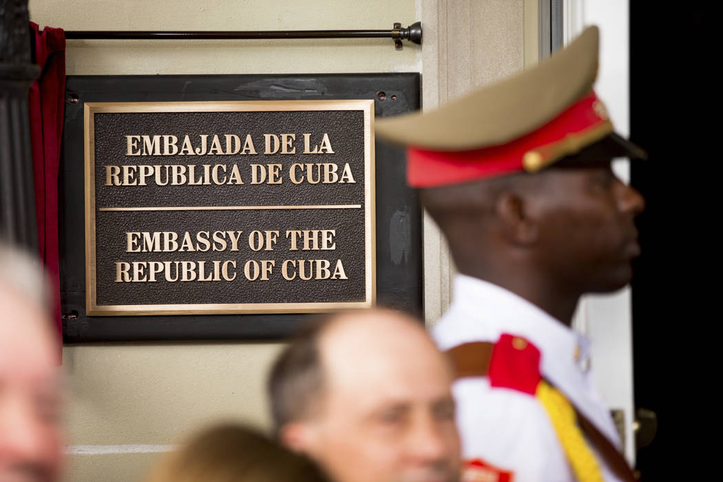 In this july 20, 2015 file photo, a member of the Cuban honor guard stands next to a new plaque at the front door of the newly reopened Cuban embassy in Washington. The State Department has expell ...