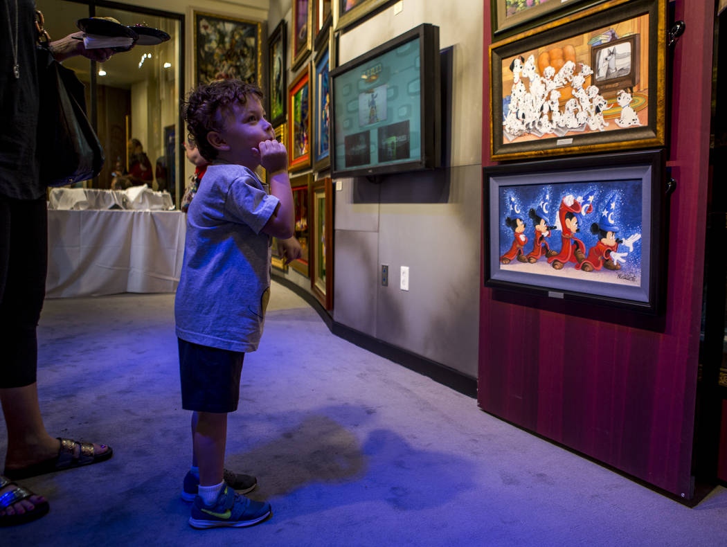 Gus Karris, 4, enjoys Mickey Mouse art while wearing his Mickey Mouse shirt during the grand opening of the Magical Memories Disney Fine Art Gallery in the Forum Shops at Caesars on Thursday, Aug. ...