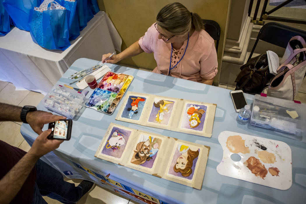 Artist Michelle St. Laurent works on watercolors during the grand opening of the Magical Memories Disney Fine Art Gallery in the Forum Shops at Caesars on Thursday, Aug. 10, 2017.  Patrick Connoll ...