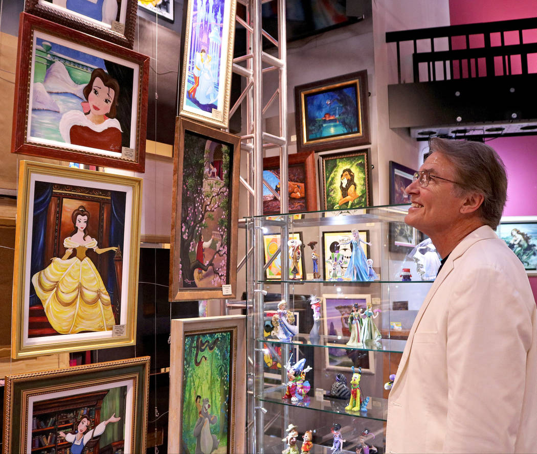 "Richard White, the voice of Gaston in the Disney animated film ""Beauty and the Beast,"" observes oil paintings of the movie's characters at the media preview for the New Magical M ..."