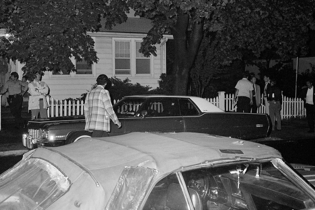 Detectives investigate the area around a parked car where a young couple was wounded June 26, 1977, in the Bayside neighborhood of the Queens borough of New York during the Son of Sam killing spre ...
