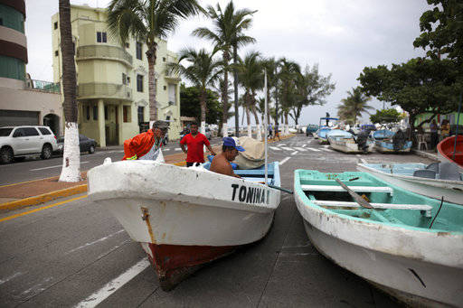 Fishermen move their boats, normally moored in the Gulf of Mexico, onto a coastal road to protect them ahead of the arrival of Hurricane Franklin, in the port city of Veracruz, Mexico, Wednesday,  ...
