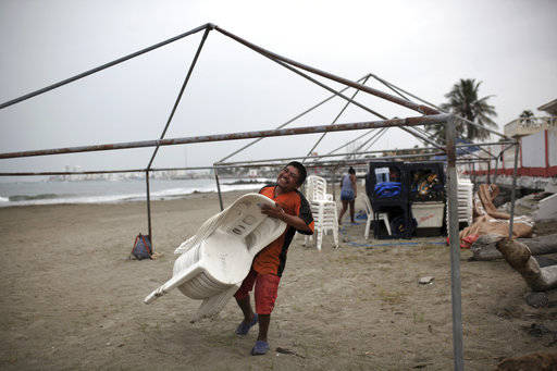 A man carries away plastic chairs as beachfront businesses strip down to their bare bones in preparation for the arrival of Hurricane Franklin, in the port city of Veracruz, Mexico, Wednesday, Aug ...