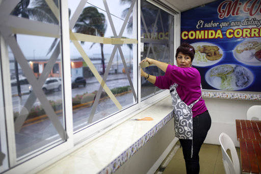 A woman tapes up the windows of her restaurant ahead of the arrival of Hurricane Franklin, in the port city of Veracruz, Mexico, Wednesday, Aug. 9, 2017. (Felix Marquez/AP)