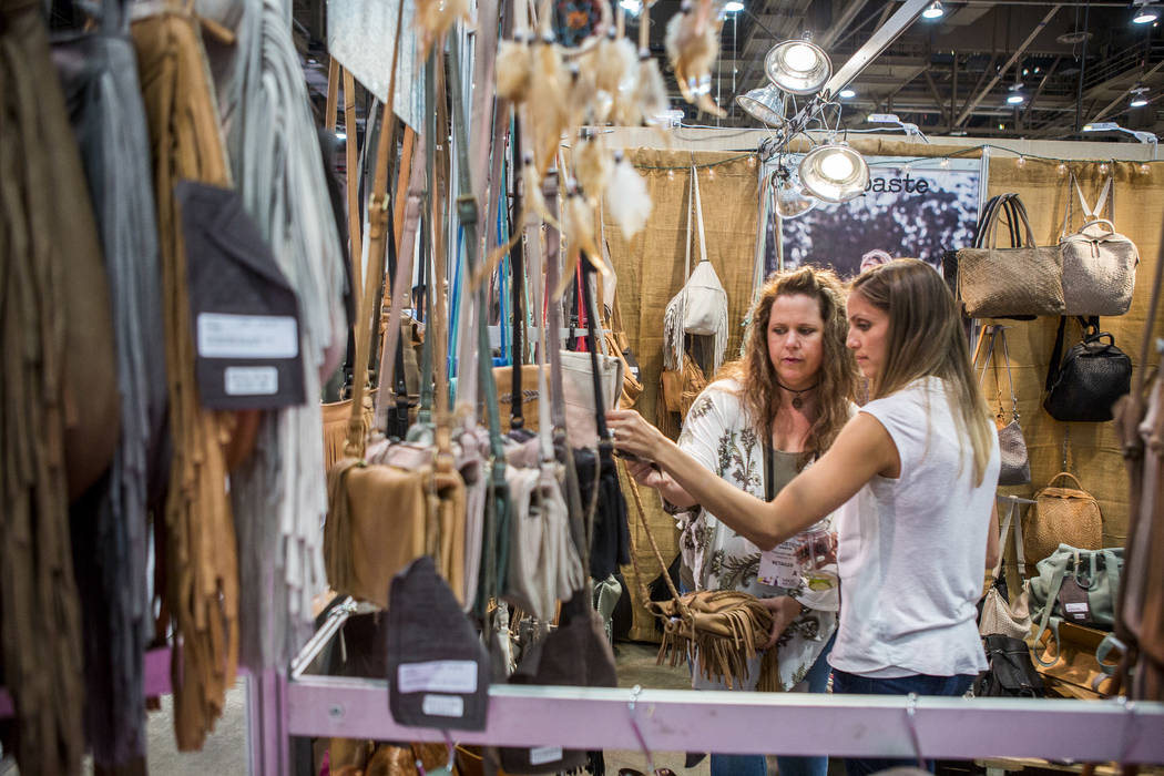 Christine Battle, right, and Christina Martin browse a selection of purses from Cut N Paste Bags at the MAGIC trade show inside the Las Vegas Convention Center on Monday, Aug. 14, 2017.  Patrick C ...