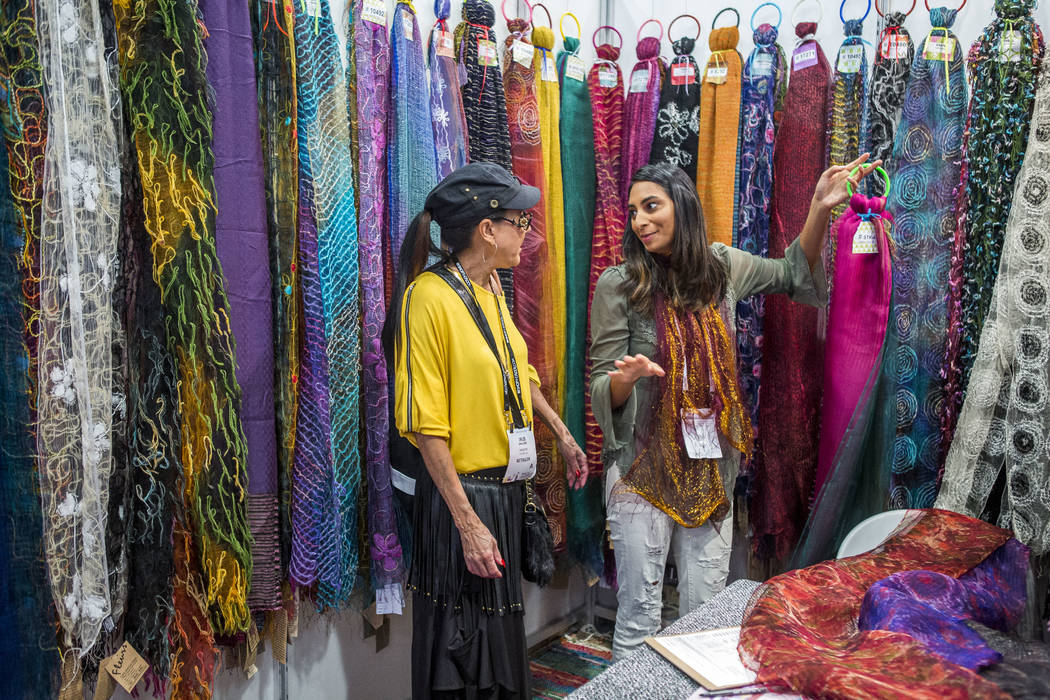 Any Sheth of Elegant Additions, right, talks with Iris Sanchez of Tucson, Ariz. about scarves at the MAGIC trade show inside the Las Vegas Convention Center on Tuesday, Aug. 15, 2017.  Patrick Con ...