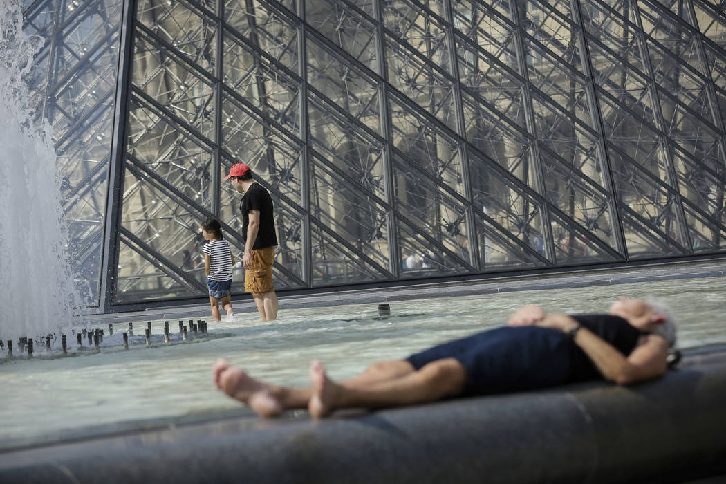 FILE - In this Aug. 26, 2016 file photo, people enjoy the weather near the Louvre Museum in Paris during a hot and sunny day. (Thomas Padilla/File, AP)