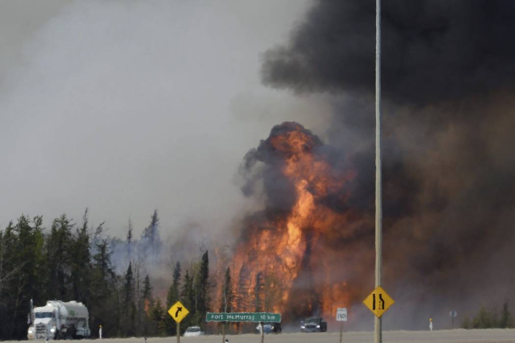 A wildfire breaks out May 6, 2016, along a highway about 10 miles south of Fort McMurray, Alberta. (Jonathan Hayward/File, The Canadian Press via AP)
