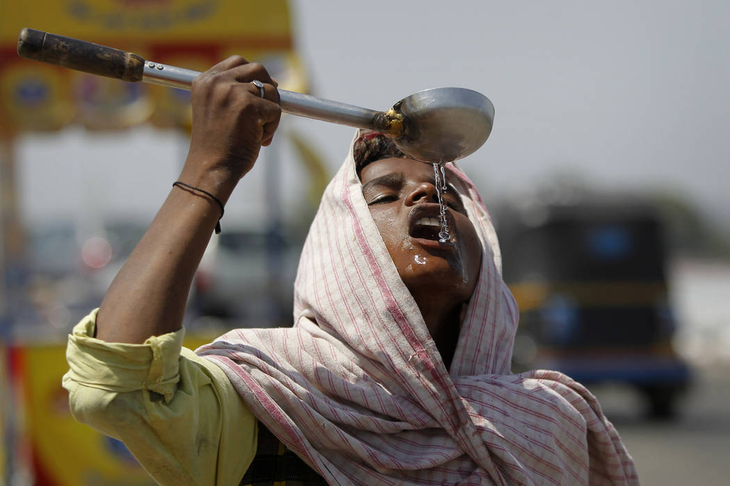 A street vendor drinks water on a hot afternoon May 27, 2016, on the outskirts of Jammu, India. A new U.S. report says last year's weather was far more extreme or record breaking than anything a ...