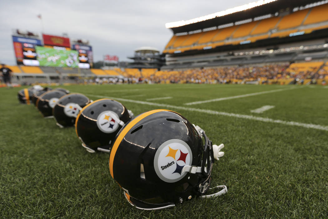 A row of Pittsburgh Steelers helmets are on the sideline at the start of an NFL training camp football practice at Heinz Field, Sunday, Aug. 6, 2017, in Pittsburgh. (AP Photo/Keith Srakocic)