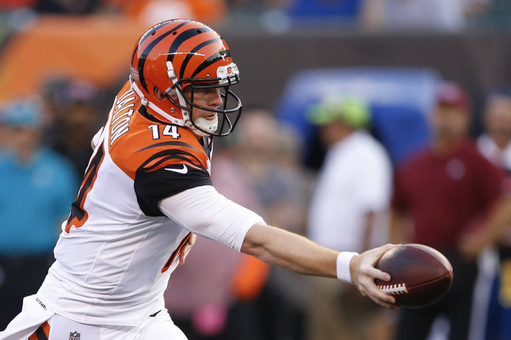 Cincinnati Bengals quarterback Andy Dalton looks to hand off the ball in the first half of a preseason NFL football game against the Tampa Bay Buccaneers, Friday, Aug. 11, 2017, in Cincinnati. (AP ...
