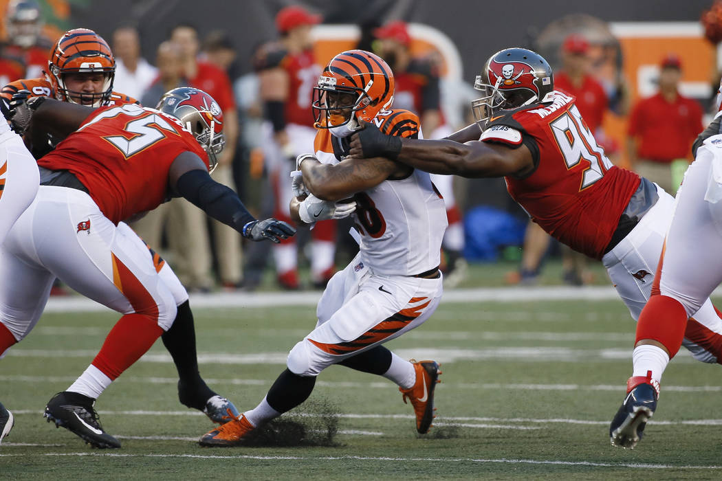 Cincinnati Bengals running back Joe Mixon, center, is tackled by Tampa Bay Buccaneers defensive tackle Clinton McDonald, right, during the first half of a preseason NFL football game, Friday, Aug. ...