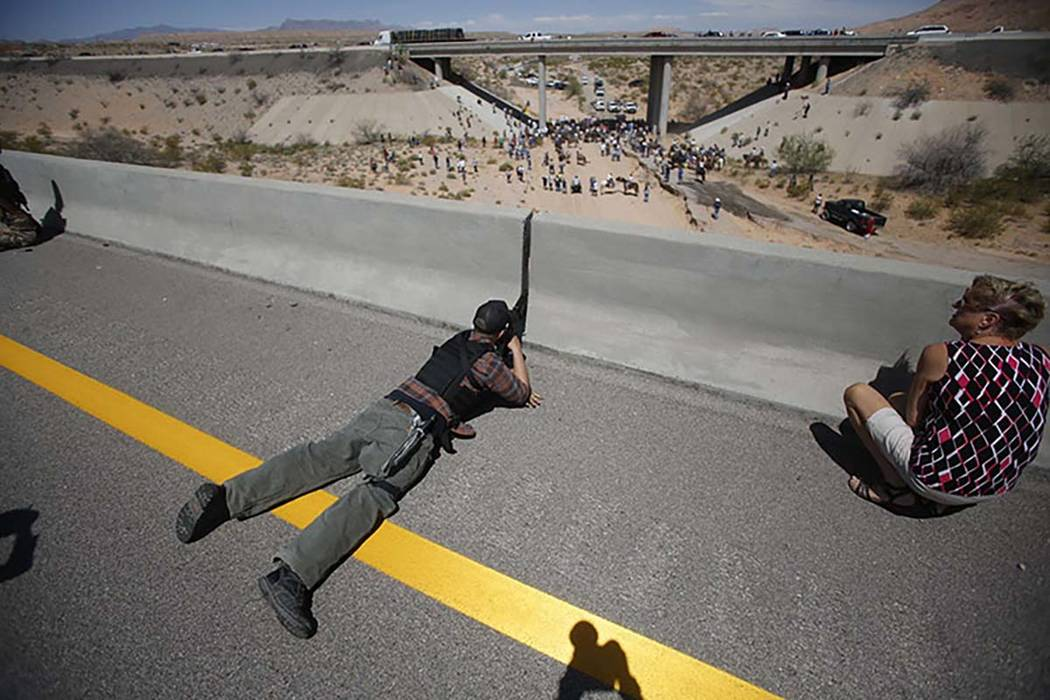 Eric Parker from central Idaho aims his weapon from a bridge as protesters gather by the Bureau of Land Management's base camp, where cattle that were seized from rancher Cliven Bundy were being h ...