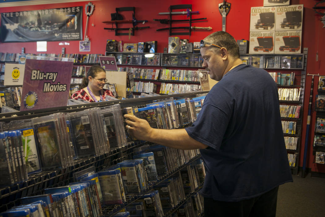 Customers at a Vintage Stock store in Kansas City, Missouri, look through a selection of movies. Vintage Stock is one of two companies owned by Las Vegas Valley-based holding company Live Ventures ...