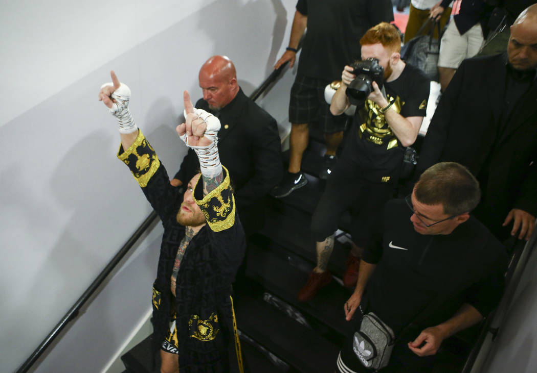 UFC fighter Conor McGregor is escorted out after a workout ahead of his boxing match against Floyd Mayweather Jr., slated for Aug. 26, at the UFC Performance Institute in Las Vegas on Friday, Aug. ...
