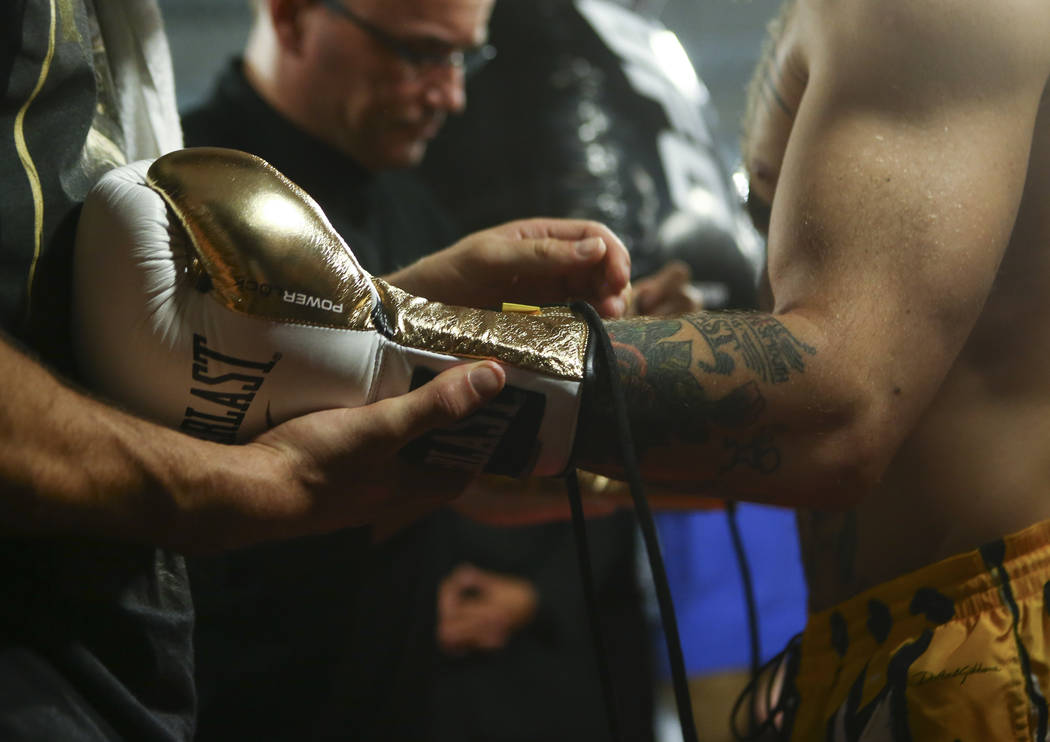 UFC fighter Conor McGregor gets a boxing glove on during a workout ahead of his boxing match against Floyd Mayweather Jr., slated for Aug. 26, at the UFC Performance Institute in Las Vegas on Frid ...