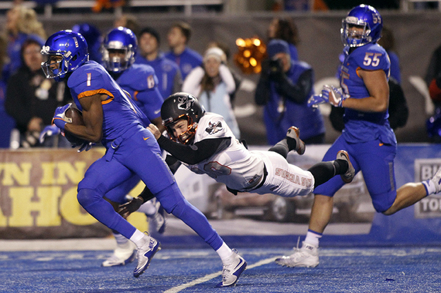 Boise State wide receiver Cedrick Wilson (1) is brought down at the end of a 74-yard punt return by UNLV kicker Evan Pantels during the first half of an NCAA college football game in Boise, Idaho, ...