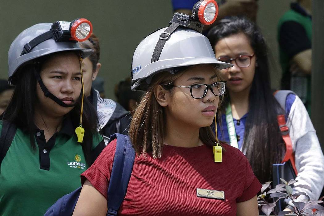 Office workers wear protective gear as they evacuate their building after an earthquake was felt in Manila, Philippines on Friday, Aug. 11, 2017. (Aaron Favila/AP)