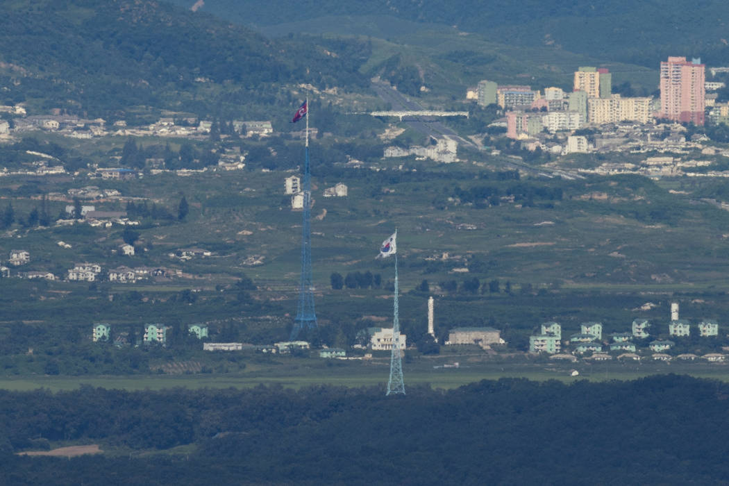 A giant North Korean flag, left, atop a 160-meter (525-foot) tower in North Korea and a South Korean flag, right, atop of a 100-meter (328-foot) tower in South Korea, flutter in the wind as pictur ...