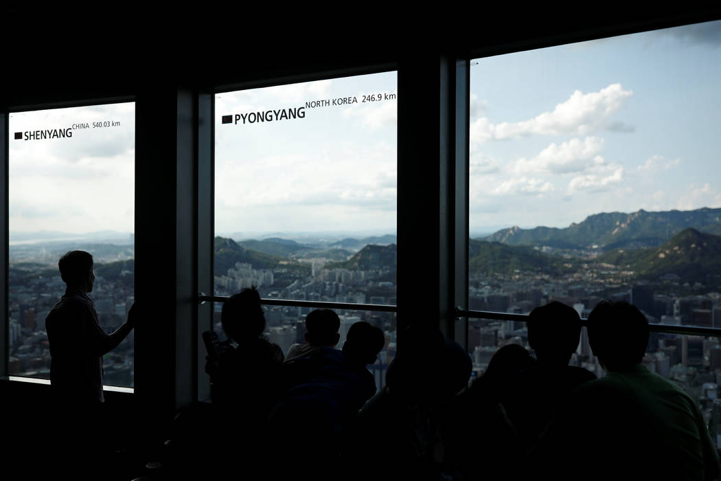 People look at the central Seoul through a window bearing the distance between Pyongyang and Seoul at an observation platform in Seoul South Korea