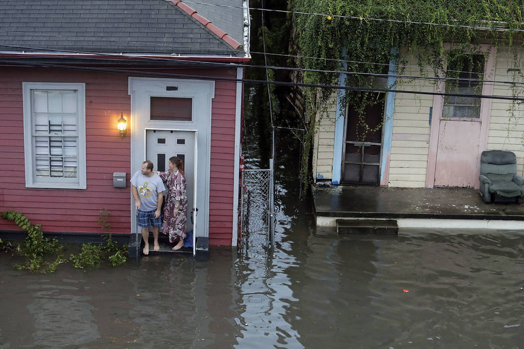 People stand outside their home in floodwaters in New Orleans on Saturday, Aug. 5, 2017. New Orleans Mayor Mitch Landrieu's office said early Thursday, Aug. 10, 2017, the city has lost service to  ...