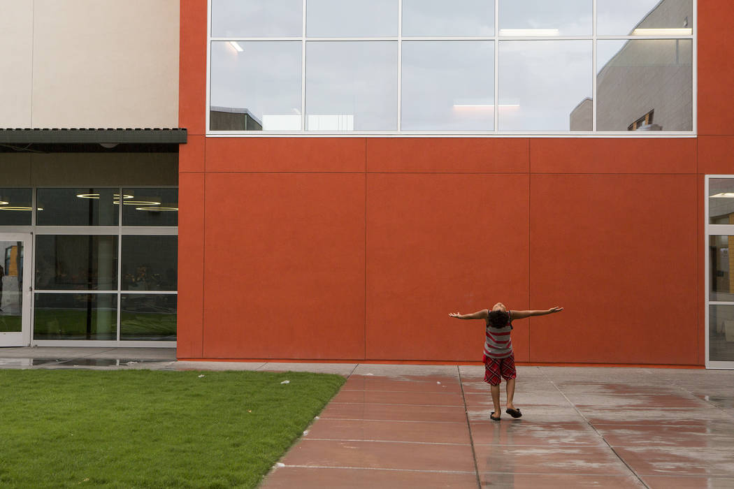 Donovan Chapman, 8, holds his arms out as raindrops fall down on him during an open house at the newly rebuilt Rex Bell Elementary School on Friday, Aug. 11, 2017. (Bridget Bennett/Las Vegas Revie ...