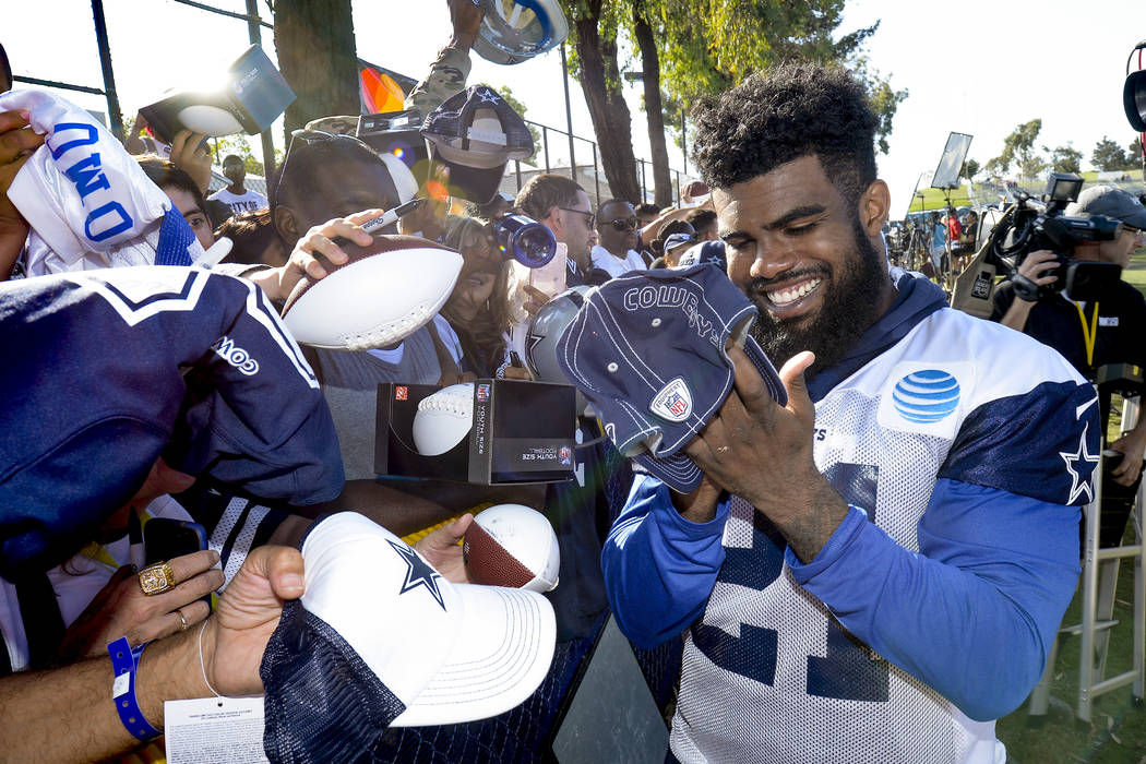 Dallas Cowboys running back Ezekiel Elliott signs autographs at the end of the day at NFL football training camp in Oxnard, Calif., Tuesday, July 25, 2017. (AP Photo/Gus Ruelas)