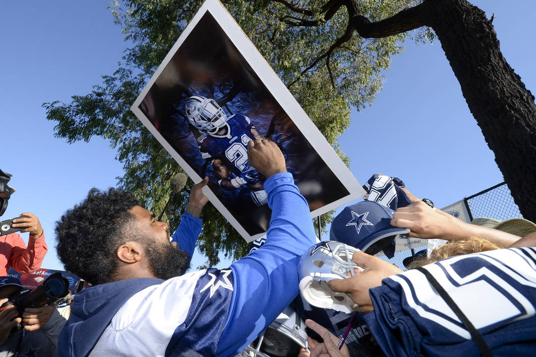 Dallas Cowboys running back Ezekiel Elliott signs autographs at the end of NFL football training camp in Oxnard, Calif., Tuesday, July 25, 2017. (AP Photo/Gus Ruelas)