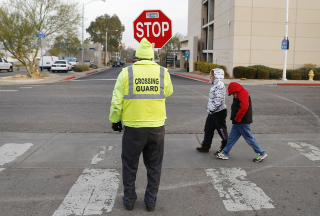 Jerry Enlow, 74, crossing guard, assists students across the street at the corner of Basic Road and Lead Street in Henderson, near McCaw Elementary School. (Bizuayehu Tesfaye/Las Vegas Review-Journal)