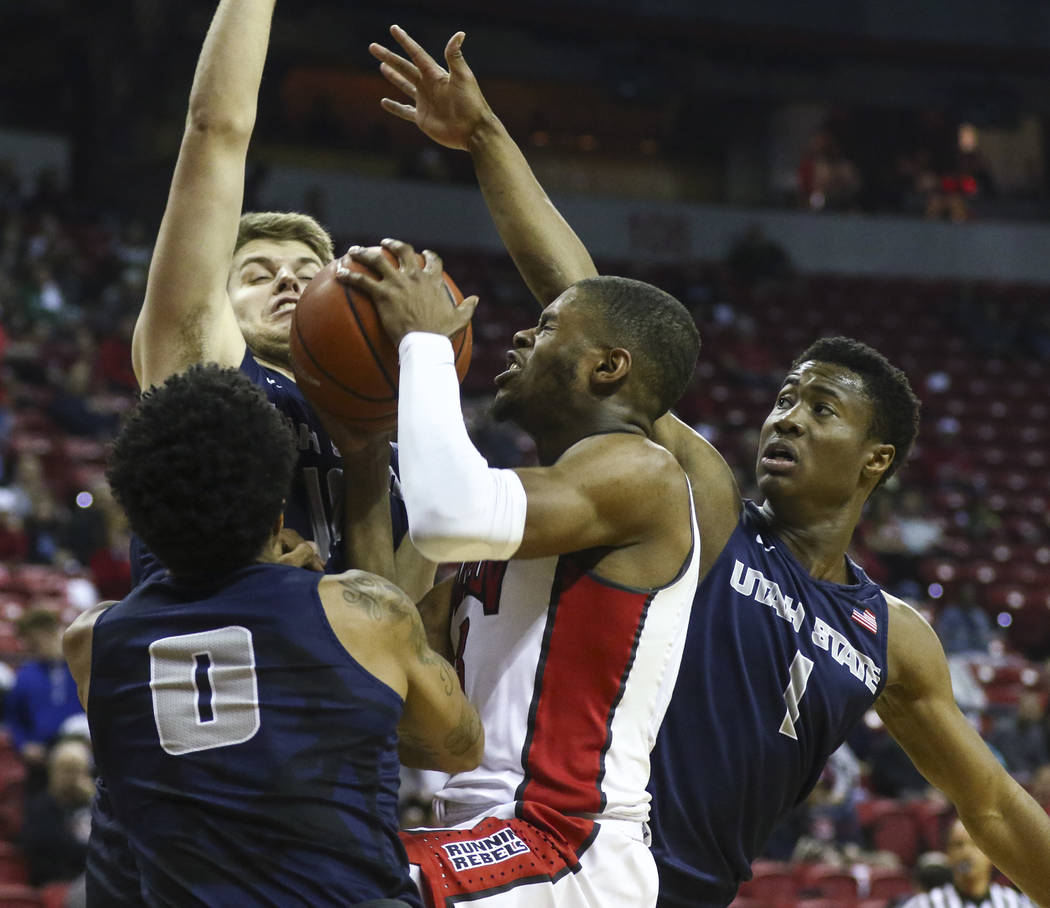 UNLV forward Tyrell Green (3) waits for a clean shot as Utah State players Shane Rector (0), Quinn Taylor (10) and Koby McEwen (1) defend during a basketball game at the Thomas & Mack Center i ...