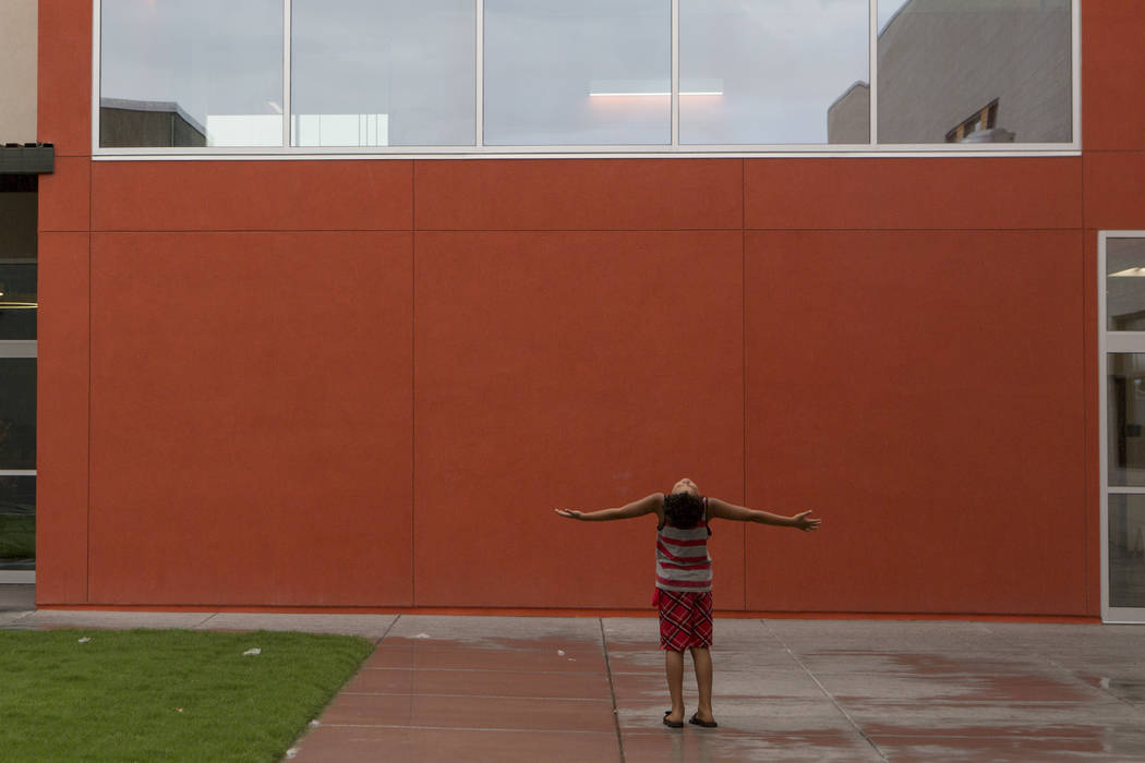 Fourth grader Donovan Chapman, 8, holds his arms out as raindrops fall down on him at the newly rebuilt Rex Bell Elementary School in Las Vegas on Friday, Aug. 11, 2017. Bridget Bennett Las Vegas  ...