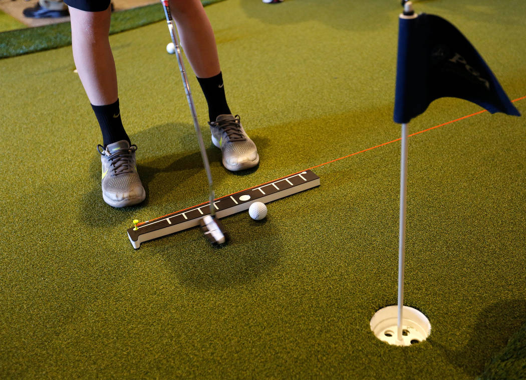 PGA 2017 Fashion & Demo Experience attendee Elliot Wallace, 13, of Stockton, Calf., putts the ball using INPUTT, a putting training device, at Topgolf in Las Vegas, Monday, Aug. 14, 2017. (Chi ...