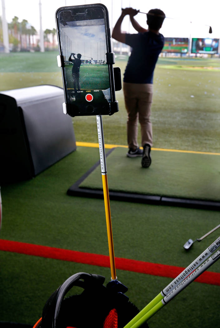 Luis Kim of SelfieGOLF USA demonstrates their cell phone clip system SelfieGOLF during PGA 2017 Fashion & Demo Experience at Topgolf in Las Vegas, Monday, Aug. 14, 2017. (Chitose Suzuki/Las Ve ...