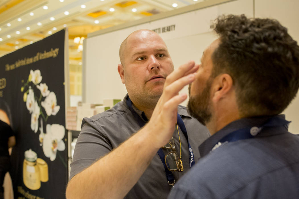 Tal Minke with Tutti Beauty demonstrates their skin care product on an attendee of the PGA Fashion and Demo Experience at The Venetian in Las Vegas, Tuesday, Aug. 15, 2017. (Elizabeth Brumley/Las  ...