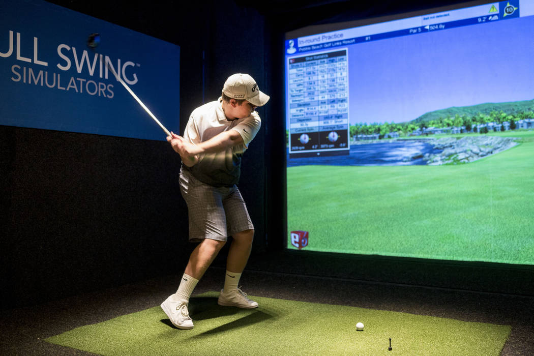 Jeffery Winkler, an attendee of the PGA Fashion and Demo Experience, golfs in the Full Swing Simulator at The Venetian in Las Vegas, Tuesday, Aug. 15, 2017. (Elizabeth Brumley/Las Vegas Review-Jou ...