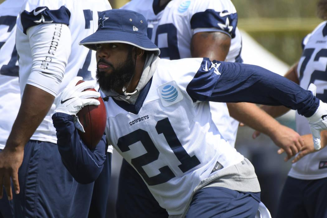 Dallas Cowboys running back Ezekiel Elliott (21) bursts through an opening during practice at the NFL football team's training camp in Oxnard, Calif., Monday, July 24, 2017. (AP Photo/Michael Owen ...