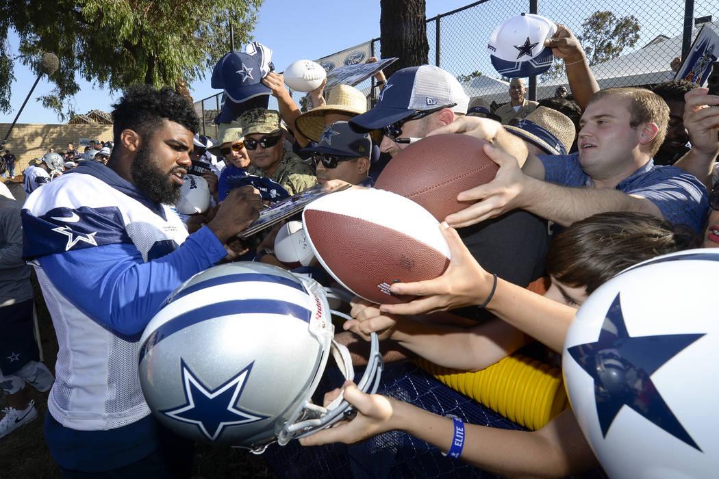 Dallas Cowboys running back Ezekiel Elliott signs autographs at the end of NFL football training camp in Oxnard, Calif., Tuesday, July 25, 2017. (AP Photo/Gus Ruelas)