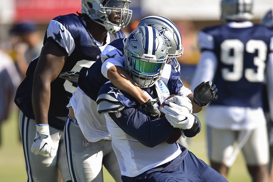 Dallas Cowboys outside linebacker Kyle Wilber, back, grabs running back Ezekiel Elliott, front, as they run a play during NFL football training camp in Oxnard, Calif., Wednesday, July 26, 2017. (A ...