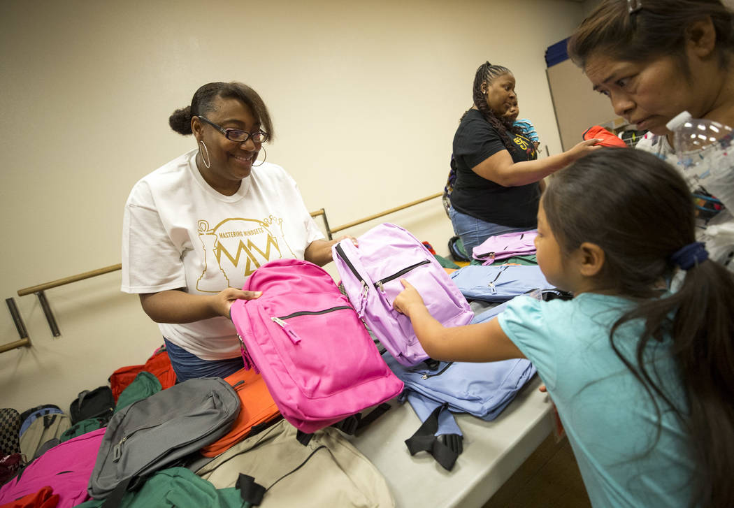 Volunteer Janay Lockhart, left, gives a backpack to first-grader Valentina Gonzaga, 6, during a back-to-school fair hosted by the Metropolitan Police Department held at the Dula Gymnasium in downt ...