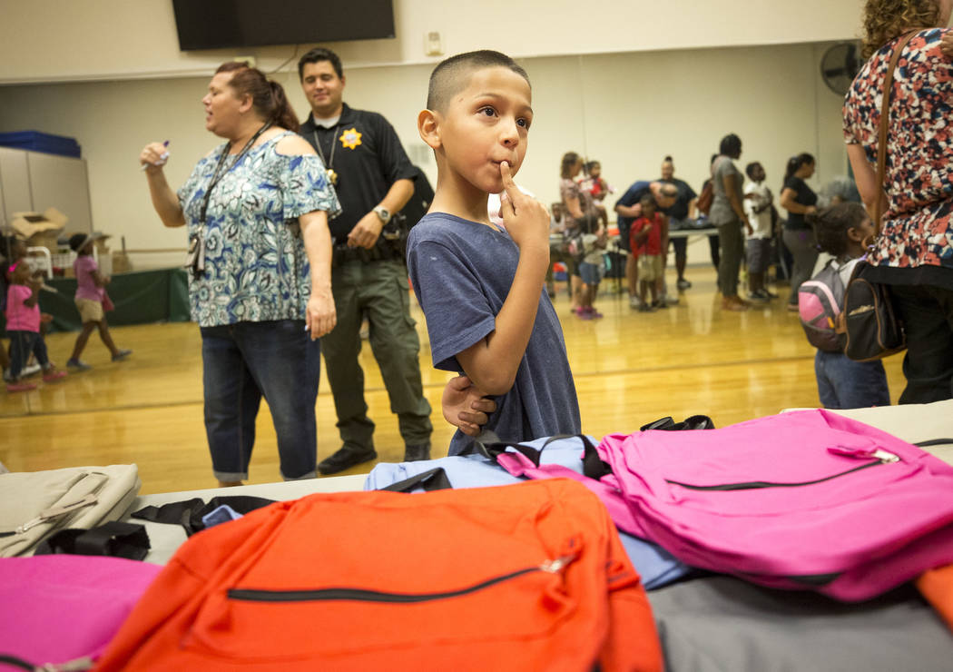 Third-grader Marcos Cruz thinks about his color options before choosing a green backpack during a back-to-school fair hosted by the Metropolitan Police Department held at the Dula Gymnasium in dow ...