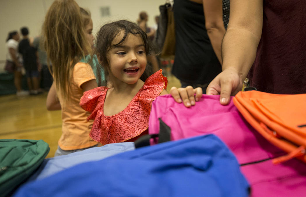 Kindergartner Gabriella McClain, 5, chooses a pink backpack during a back-to-school fair hosted by the Metropolitan Police Department held at the Dula Gymnasium in downtown Las Vegas on Saturday,  ...