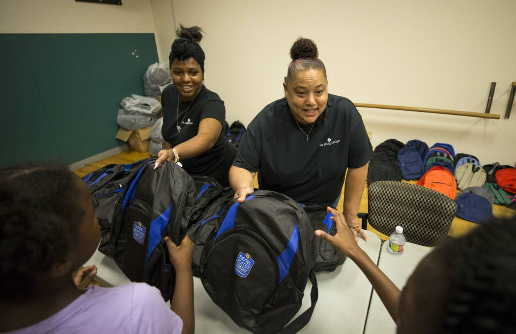 Volunteers with The Siegel Group Rose Brown, left, Ronda Armstrong distribute free backpacks to children during a back-to-school fair hosted by the Metropolitan Police Department held at the Dula  ...