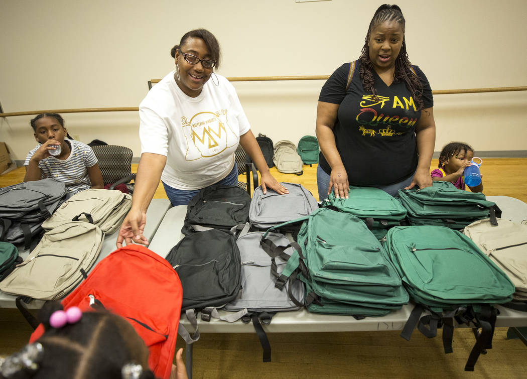 Volunteers with the Mastering Mindsets Janay Lockhart, left, and Tuyuana Fondren distribute backpacks to kids during a back-to-school fair hosted by the Metropolitan Police Department held at the  ...